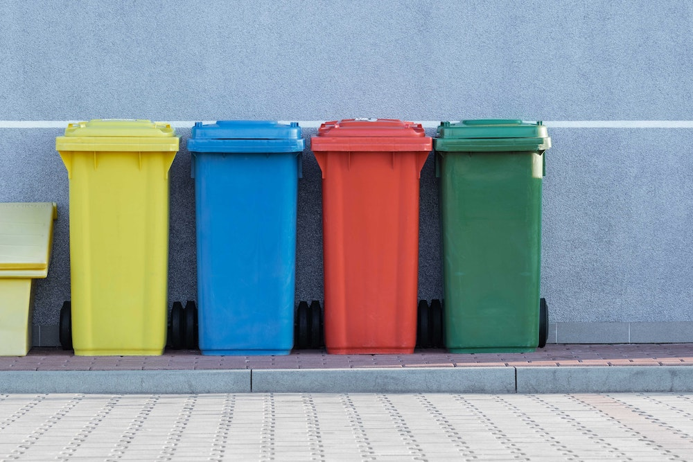 Bins on a curb for trash, recycling, and compost.